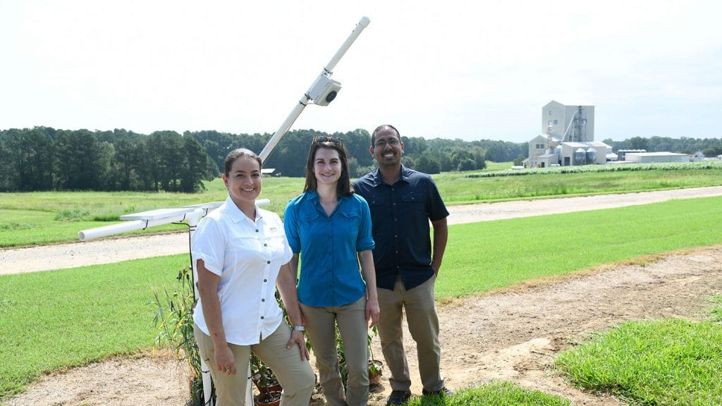 Three researchers in front of a white box on a pole mounted at the Lake Wheeler University Field Lab.